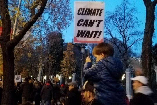 "Kind mit Schild ""Climate can't wait""."