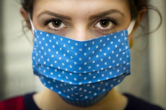 Junge Frau mit ernstem Blick und geblümtem Mundschutz