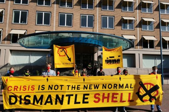 "Protestierende vor Shell-Gebäude mit gelbem Transparent: ""Crisis is not the new normal – dismantle Shell!"""